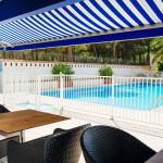 Le solarium avec vue sur la piscine de l'hôtel -Hôtel Plage des Pins